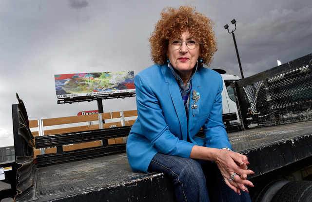 Artist Diane Bush sits beneath a 40-foot-wide billboard featuring her artwork May 6, 2016, in North Las Vegas. Las Vegas Valley roadside billboards that have not been rented are featuring removabl ...