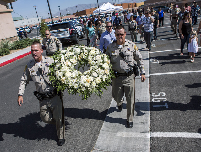 Metro officers Steve Haugh, left, and Troy Nicol carry a wreath for civilian Joseph Wilcox,  who was gunned down two years ago, during a memorial dedication at Walnut Park, 3075 North Walnut Rd.,  ...