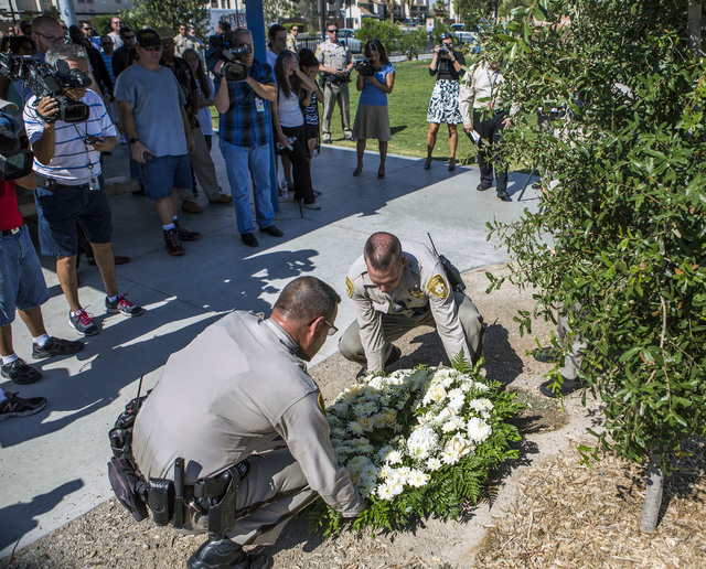 Metro officers Troy Nicol, left, and Steve Haugh lays a wreath for civilian Joseph Wilcox,  who was gunned down two years ago, during a memorial plaque dedication at Walnut Park, 3075 North Walnut ...