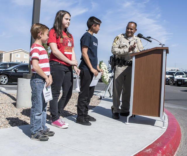 Metro Sgt. Jose Hernandez, right, honors students Nathan Law, Samantha Criswell and Isaac Ortiz for the winning entries in police art contest during a ceremony remembering officers Igor Soldo and  ...