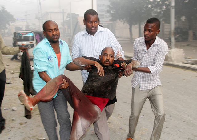 Somali men help a wounded civilian who was wounded in a suicide car bomb attack on a hotel in Mogadishu, Somalia, Saturday, June 25, 2016. (Farah Abdi Warsameh/The Associated Press)