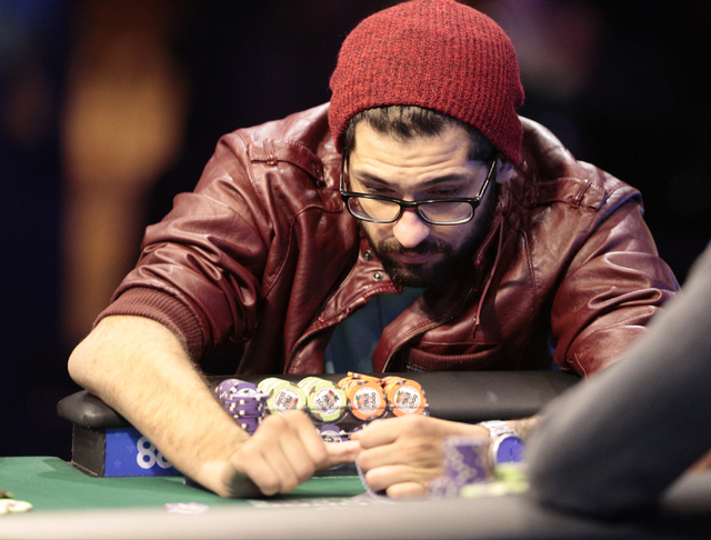 Tournament participant Garrett Greer glances at his cards during the World Series of Poker $1,500 Millionaire Maker No-Limit Hold'em final table at the Rio Convention Center in Las Vegas on Tuesda ...