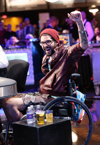 Tournament participant Garrett Greer raises his hand in celebration after a win against Lisa Meredith during the World Series of Poker $1,500 Millionaire Maker No-Limit Hold'em final table at the  ...