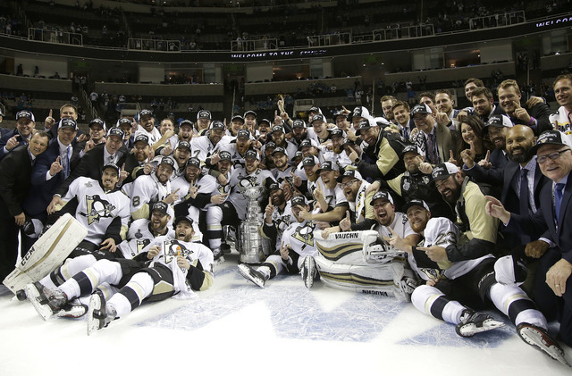 Pittsburgh Penguins players and coaches pose for photos with the Stanley Cup after Game 6 of the NHL hockey Stanley Cup Finals against the San Jose Sharks in San Jose, Calif., Sunday, June 12, 201 ...