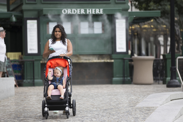 A woman pushes a stroller near New York-New York hotel-casino on Tuesday, June 21, 2016, in Las Vegas. The Clark County Commission on Tuesday approved a bag ban that will also includes strollers d ...
