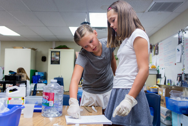 Kendall Allgower, left, and Avery Sanford, fifth-grade students at John C. Vanderburg Elementary School, work on a seed experiment at their school in Henderson Thursday, June 23, 2016 that astrona ...