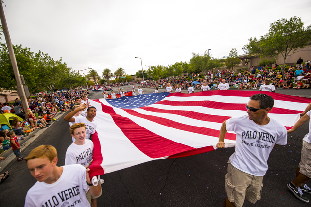 A giant American flag is carried by Palo Verde High School's cross country team during the Fourth of July parade in Summerlin on Saturday, July 4, 2015. (Joshua Dahl/Las Vegas Review-Journal)