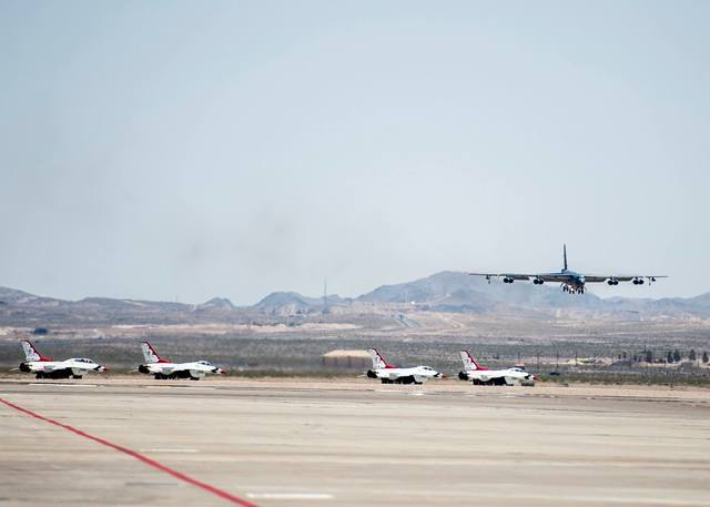 Four F-16 jets from the Thunderbirds air demonstration team taxi for takeoff as a B-52 bomber approaches on June 7, 2016, at the Nellis Air Force Base in Las Vegas. Photo courtesy of the U.S. Air  ...