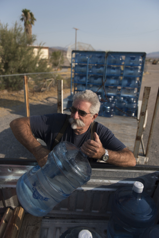 Larry Levy, fire chief with Southern Inyo Fire Protection District, lifts a jug of potable water out of his truck bed as he makes his weekly delivery rounds to residents in Tecopa, Calif. Tuesday, ...
