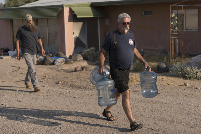 Larry Levy, fire chief with Southern Inyo Fire Protection District, right, and Jim Furlough, make their weekly potable water delivery rounds to residents in Tecopa, Calif. Tuesday, June 21, 2016.  ...