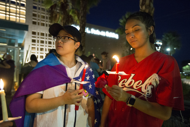 Alyssa Buhay, left, and girlfriend Nita Castro attend a candle light vigil honoring the victims of the Orlando mass shooting at the The Gay and Lesbian Community Center of Southern Nevada on Sunda ...