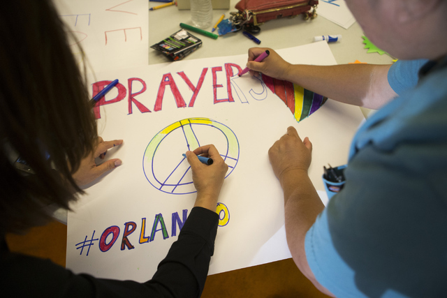 Attendees make signs before the candle light vigil to honor victims of the Orlando mass shooting at the The Gay and Lesbian Community Center of Southern Nevada on Sunday, June 12, 2016, in Las Veg ...