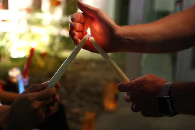 Attendees hold candles during the candle light vigil honoring victims of the Orlando mass shooting at the The Gay and Lesbian Community Center of Southern Nevada on Sunday, June 12, 2016, in Las V ...