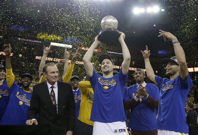 Former NBA player Rick Barry, center left, watches as Golden State Warriors guard Klay Thompson, center, Stephen Curry, right, and their teammates celebrate after winning the Western Conference fi ...