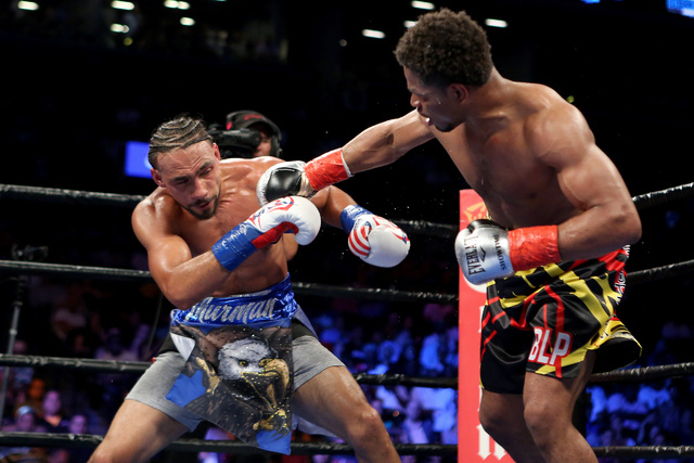 Keith Thurman, left, absorbs a right hand against Shawn Porter during their WBA Welterweight title fight at the Barclays Center in Brooklyn borough of New York on Saturday, June 25, 2016. Thurman  ...