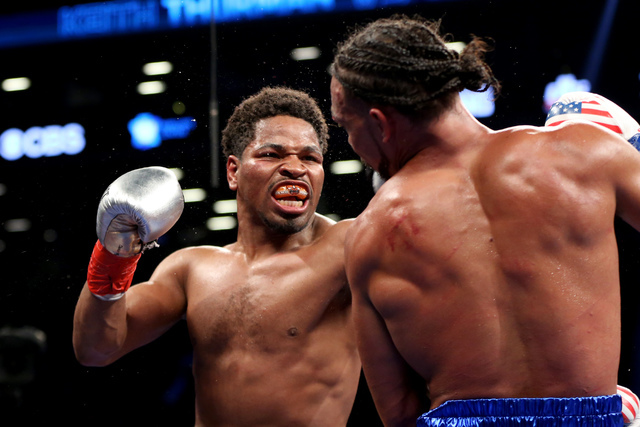 Shawn Porter, left, trades punches with Keith Thurman during their WBA Welterweight title fight at the Barclays Center in Brooklyn borough of New York on Saturday, June 25, 2016. Thurman won via u ...