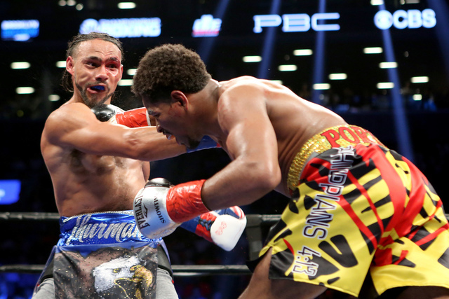 Keith Thurman, left, takes a right hand from Shawn Porter during their WBA Welterweight title fight at the Barclays Center in Brooklyn borough of New York on Saturday, June 25, 2016. Thurman won v ...