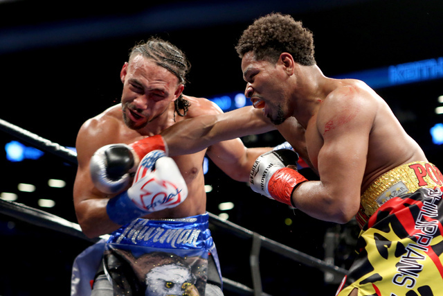 Keith Thurman absorbs a right hand from Shawn Porter during their WBA Welterweight title fight at the Barclays Center in Brooklyn borough of New York on Saturday, June 25, 2016. Thurman won via un ...