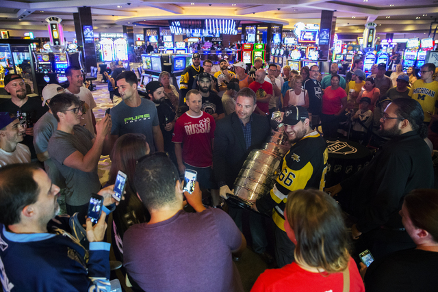 Howie Borrow, middle, a cup keeper with the Hockey Hall of Fame, posses for photos with the Stanley Cup Monday, June 20, 2016, at the Hard Rock Hotel in Las Vegas. Benjamin Hager/Las Vegas Review- ...