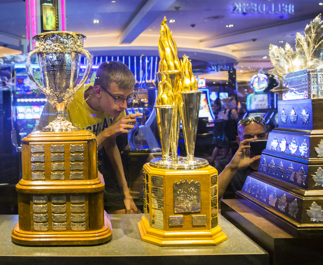 Kyle Boes, left, takes a look at the Conn Smythe Trophy Monday, June 20, 2016, at the Hard Rock Hotel in Las Vegas. Benjamin Hager/Las Vegas Review-Journal