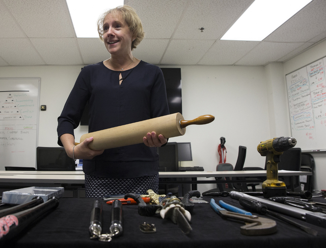 Lorie Dankers, a spokeswoman for the Transportation Security Administration, holds a large rolling pin that was recently confiscated by TSA agents at McCarran International Airport on Monday, June ...