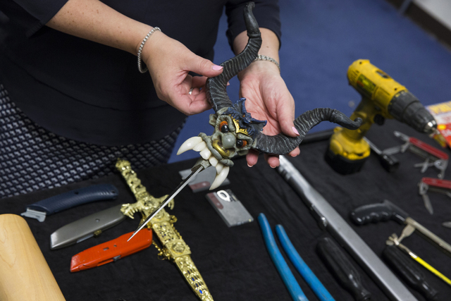 Lorie Dankers, a spokeswoman for the Transportation Security Administration, holds a novelty knife that was recently confiscated by TSA agents at McCarran International Airport on Monday, June 27, ...