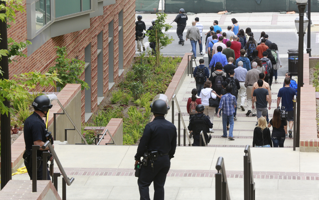 Los Angeles Police officers escort people at the UCLA campus after a fatal shooting at the University of California, Los Angeles, Wednesday, June 1, 2016, in Los Angeles. Los Angeles police chief  ...