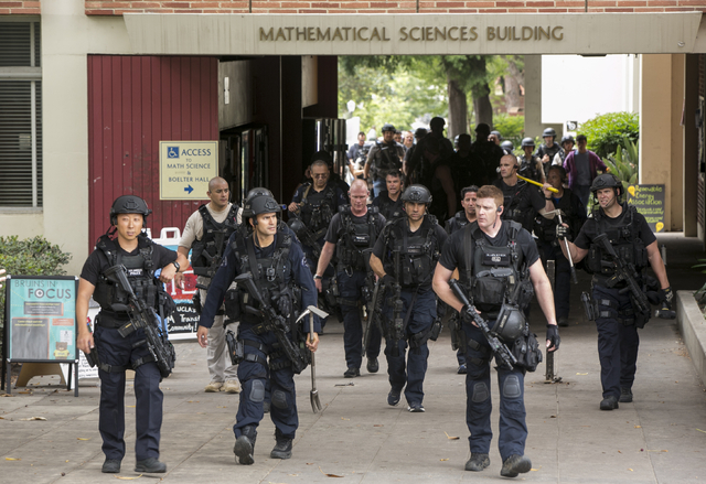 Los Angeles Police officers walk by the Mathematical Sciences Building on the UCLA campus after a fatal shooting at the University of California, Los Angeles, Wednesday, June 1, 2016, in Los Angel ...