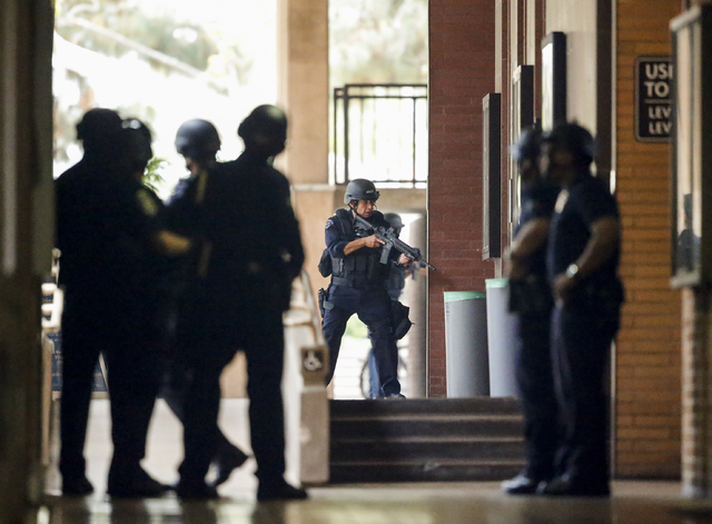 Los Angeles Police officers search the UCLA campus near the scene of a fatal shooting at the University of California, Los Angeles, Wednesday, June 1, 2016, in Los Angeles. Los Angeles police chie ...