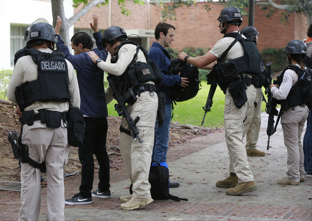 Los Angeles Police officers search students who were evacuated from the Mathematical Sciences Building at the UCLA campus near the scene of a fatal shooting at the University of California, Los An ...