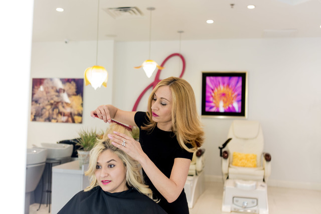 Beli Andaluz, owner and lead stylist of Beli Andaluz Salon, gives her assistant Anarely Nunez a trim at her salon in Las Vegas June 24, 2016. Elizabeth Brumley/Las Vegas Review-Journal Follow @eli ...
