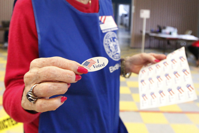 Volunteer handing out I Voted stickers. (Thinkstock)