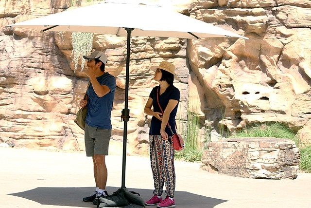 Te Li, left, and Kayee Leung, both of Santa Barbara, Calif., stand under patio umbrella as they visit Las Vegas Springs Preserve on  June 7, 2016. (Bizuayehu Tesfaye/Las Vegas Review-Journal Follo ...