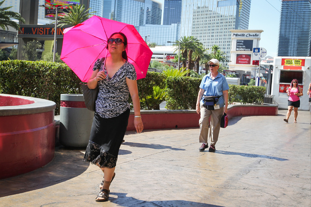 A woman walking along the Strip in triple-digit heat shields herself from the sun with an umbrella in Las Vegas on Monday, June 20, 2016. Brett Le Blanc/Las Vegas Review-Journal Follow @bleblancphoto