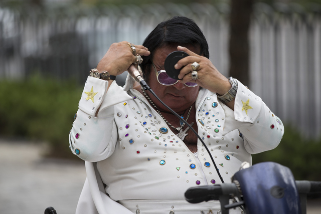 Elvis impersonator Michael Romeo combs his hair to pose with tourists near Monte Carlo hotel-casino on Tuesday, June 21, 2016, in Las Vegas. (Erik Verduzco/Las Vegas Review-Journal Follow @Erik_Ve ...