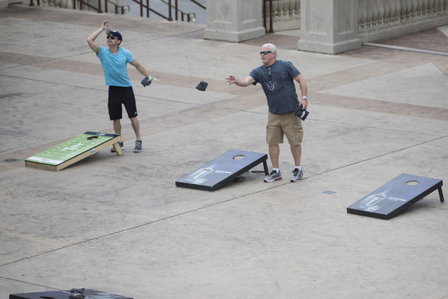 People toss bean bags to a cornhole near Caesars Palace hotel-casino on Tuesday, June 21, 2016, in Las Vegas. (Erik Verduzco/Las Vegas Review-Journal Follow @Erik_Verduzco)
