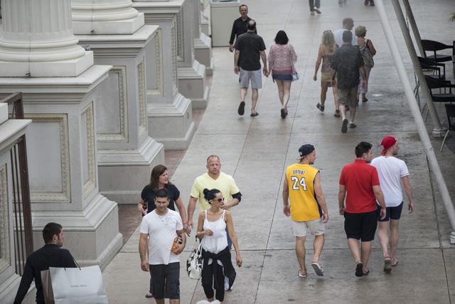 People walk near Caesars Palace hotel-casino on Tuesday, June 21, 2016, in Las Vegas. (Erik Verduzco/Las Vegas Review-Journal Follow @Erik_Verduzco)