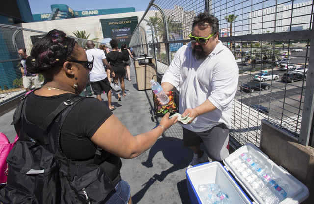 Street peddler Greg Martinez, right, exchanges a cold bottle of water for a dollar with a passer-by on a pedestrian overpass along the Las Vegas Strip on Saturday, June 25, 2016. (Richard Brian/La ...
