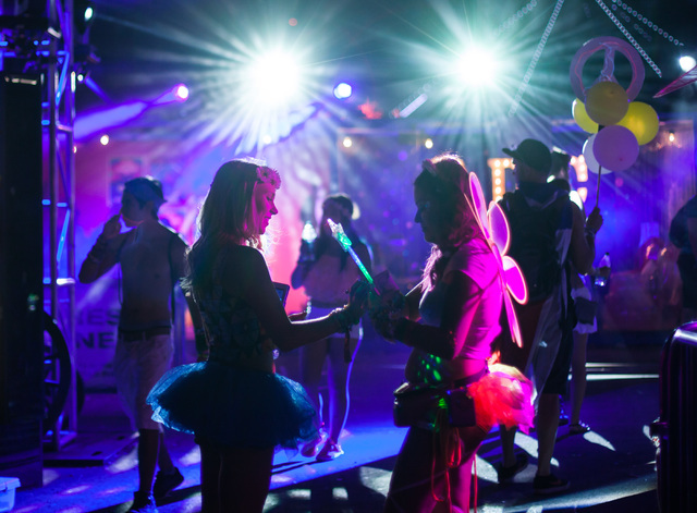 Attendees trade kanji bracelets at the Bud Light House of Whatever area at Electric Daisy Carnival at the Las Vegas Motor Speedway in Las Vegas during the early hours of Monday, June 22, 2015. (Ch ...