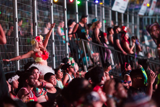 An attendee dances on a ledge near the Cosmic Meadow stage at Electric Daisy Carnival at the Las Vegas Motor Speedway in Las Vegas during the early hours of Monday, June 22, 2015. (Chase Stevens/L ...