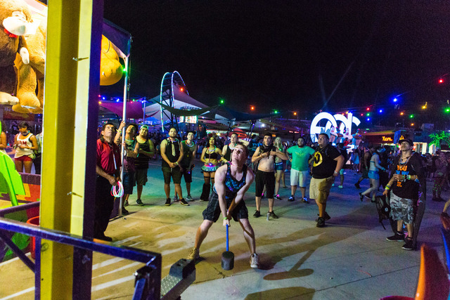 David Husky from Lake Forest, CA hits the bell playing the carnival game Strong Man during the second night of Electric Daisy Carnival at Las Vegas Motor Speedway early Sunday morning, June 19, 20 ...