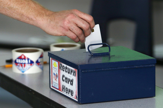 A man returns a card used for casting votes electronically in the primary election at Robert L. Forbuss Elementary School Tuesday, June 14, 2016, in Las Vegas. (Ronda Churchill/Las Vegas Review-Jo ...