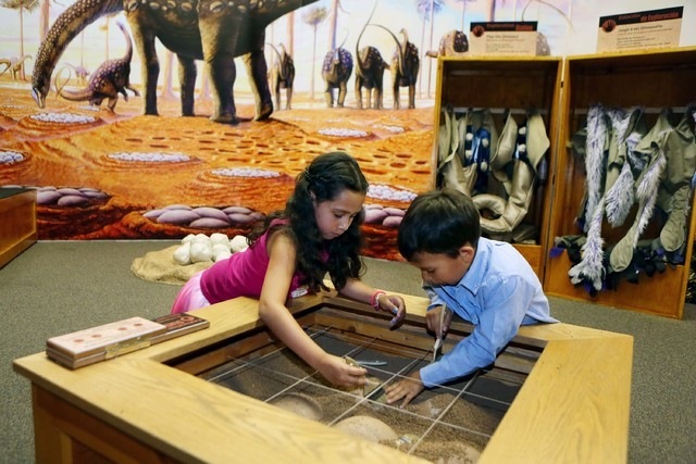 Zoey, 8, left, and Isaac Coreas, 6, play at a paleontologist exploration station for children at Las Vegas Natural History Museum July 8, 2014. Sundown in Downtown is returning for its fifth year  ...
