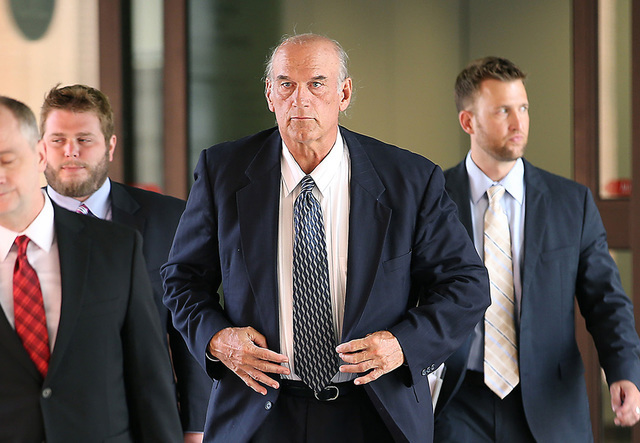 Former Minnesota Gov. Jesse Ventura, center, leaves federal court in St. Paul, Minn., July 8, 2014. A jury awarded $1.8 million to former Minnesota Gov. Jesse Ventura in his lawsuit against the es ...