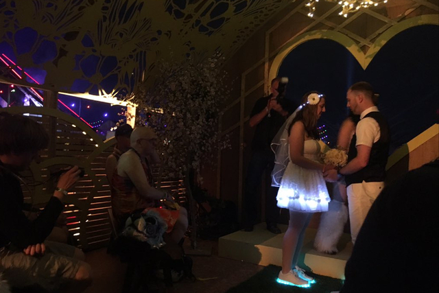 A couple exchange vows at the Chapel of Nature, a barn-like structure with a wooden roof with floral cut outs at the Electric Daisy Carnival in Las Vegas early Saturday, June 18, 2016. The ceremon ...