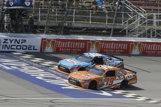 Daniel Suarez (19) passes Kyle Busch (18) in the final laps to win the NASCAR Xfinity series auto race at Michigan International Speedway, Saturday, June 11, 2016 in Brooklyn, Mich. The was the fi ...
