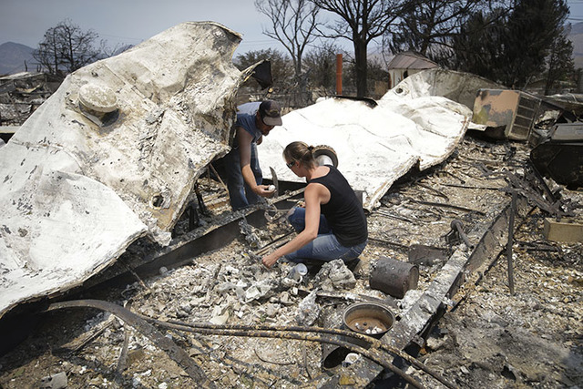 Douglas Nelson, left, shows his wife, Amy, an item he found as they survey the remains of their home devastated by a wildfire, Saturday, June 25, 2016, in South Lake, Calif. The couple said they l ...