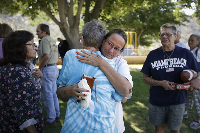 Evacuee Rene Czajka, facing camera, gets emotional as she comforts Cathy Berlin who lost her home in a wildfire as they gather for a briefing at an evacuation center, Saturday, June 25, 2016, in K ...