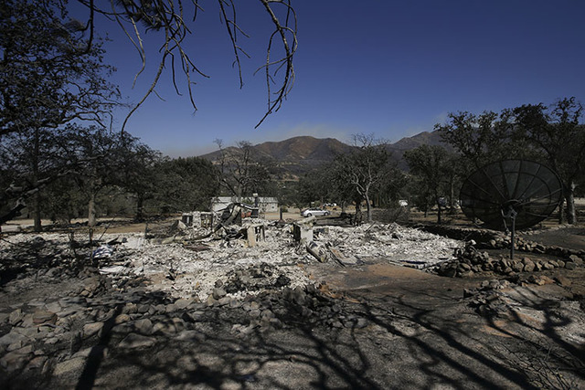 Scorched trees and debris are all that remains of a home burned by a wildfire Friday, June 24, 2016, in Mountain Mesa, Calif. (Jae C. Hong/The Associated Press)