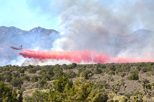 A VLAT aircraft drops retardant on a wildfire Sunday near state Route 160 and Lovell Canyon Road. (Benjamin Hager/Las Vegas Review-Journal)